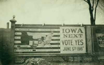 """Billboard urging Iowans to vote for women's suffrage in primary election of June 5, 1916.  Large text says, """"Iowa Next.  Vote yes June 5th 1916"""" and is next to a map of the 48 contiguous states with states where """"full suffrage"""" and """"partial suffrage"""" are indicated.  Iowa is shown as """"partial suffrage."""""""