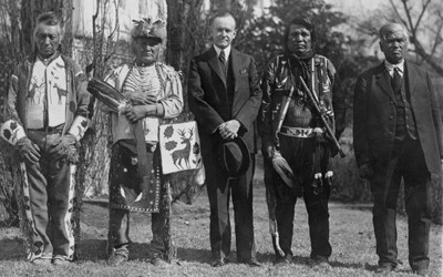 President Calvin Coolidge is seen in the center of a group of five Native American men on the south lawn of the White House.