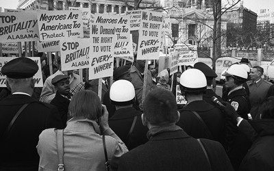 """African American demonstrators outside the White House, with signs """"We demand the right to vote, everywhere"""" and signs protesting police brutality against civil rights demonstrators in Selma, Alabama."""