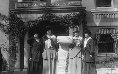 """Four women in dresses and hats proudly stand in front of a building with a sign that reads """"National Women's Party.""""  Between the two women in the center is a very large roll of paper that the women are holding up.  These National Women's Party leaders had been working to collect signatures of support on a """"mile long"""" paper to present to members of Congress."""