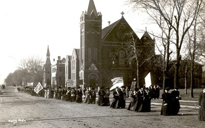 """Women's suffrage parade shown passing by church. One banner reads: """"Taxation without representation is tyranny--as true now as in 1776""""."""