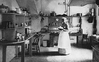One adult woman in a floor-length dress, seen in a large kitchen.  Commercial range and oven on the right, many shelves, tables, and other cooking equipment also visible.