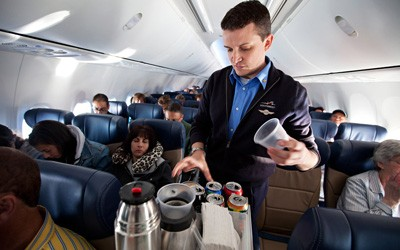 Southwest Airlines Flight Attendant serves beverages on flight