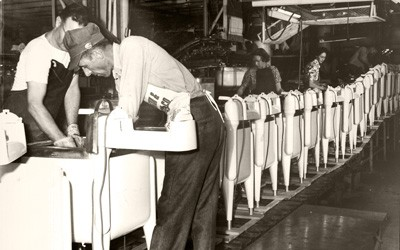 Two adult men in foreground bent over working on washing machines that are closely lined up on an assembly line.  Two women and a man are seen in the background also  working on a part of the Maytag washing machine.