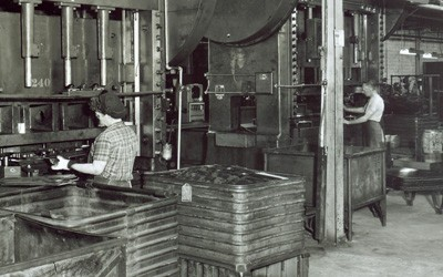 Woman in foreground standing with her back to the photographer, operating a very large boring press.