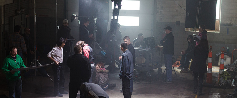 Warehouse like film set with production crew