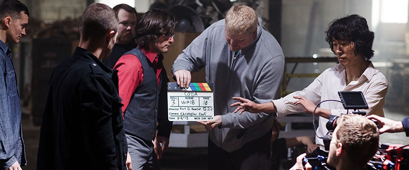 Man holding clap board in film production