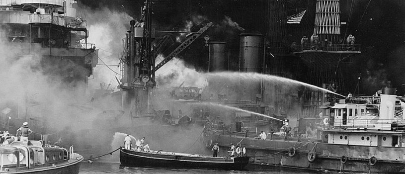 The black and white image shows the aftermath of the bombing of Pearl Harbor, Hawaii with the  USS West Virginia aflame. Disregarding the dangerous possibilities of explosions, United States sailors man their boats at the side of the burning battleship, USS West Virginia, to better fight the flames started by Japanese torpedoes and bombs. Note the national colors flying against the smoke-blackened sky