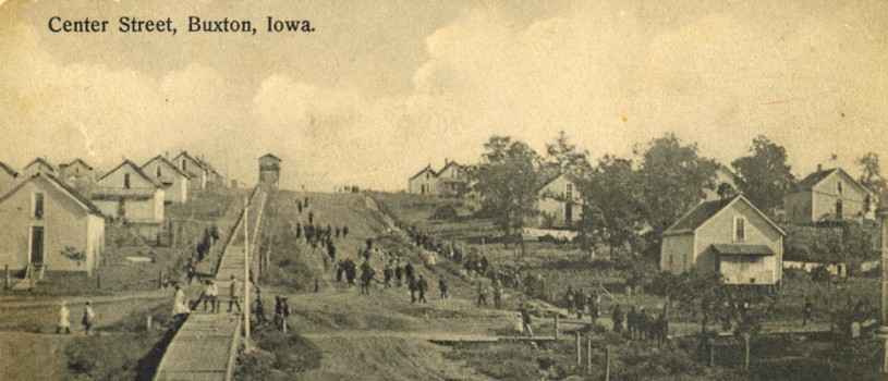 "Many people seen at a distance walking down ""Center Street"" in Buxton, Iowa, circa 1908.  Photograph shows company houses, muddy streets, ""coal chute hill,"" and many mature trees."