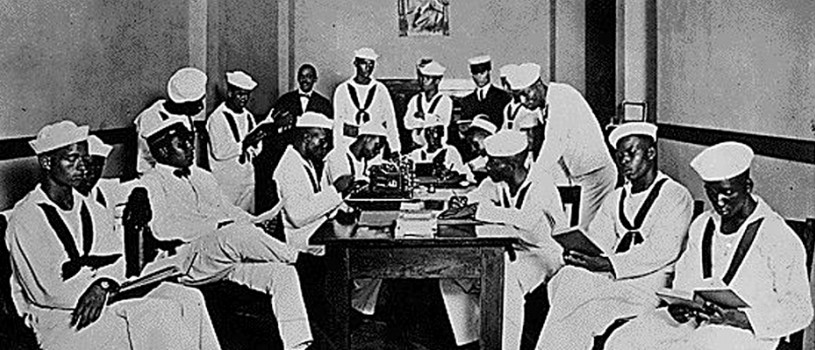 Picture of African-American soldiers and sailors sitting and standing around a table in a Red Cross Rest Room specifically outfitted for only African Americans during World War I.