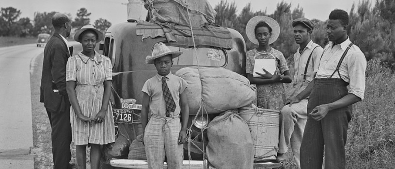 Image of Black migrants standing near their loaded-down car along a road in North Carolina as they travel from Florida to New Jersey to take jobs picking potatoes.
