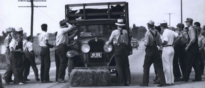 The photo depicts a bale of hay in the middle of the road blocking a truck with cows in the back bound for Sioux City with protestors on either side of the truck.