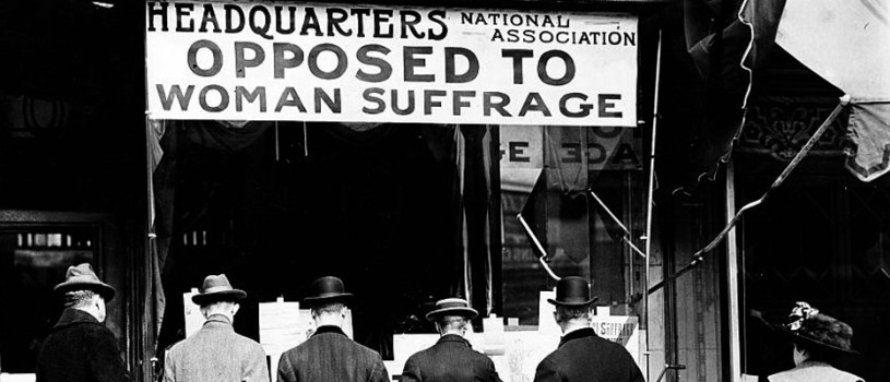 "Photograph shows men looking at material posted in the window of the National Anti-Suffrage Association headquarters while a woman looks on behind them. The sign in the window reads ""Headquarters National Association Opposed to Woman Suffrage."""