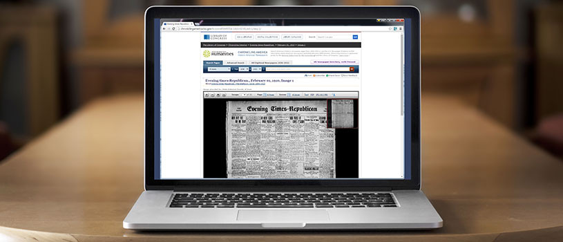 Laptop on wood table with digital newspaper project