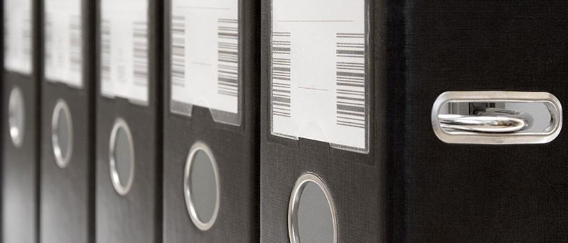 Rows of black binders with barcodes
