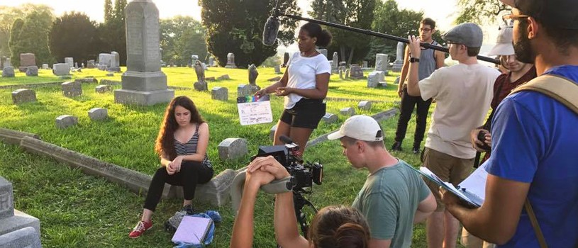 Young film crew in cemetery